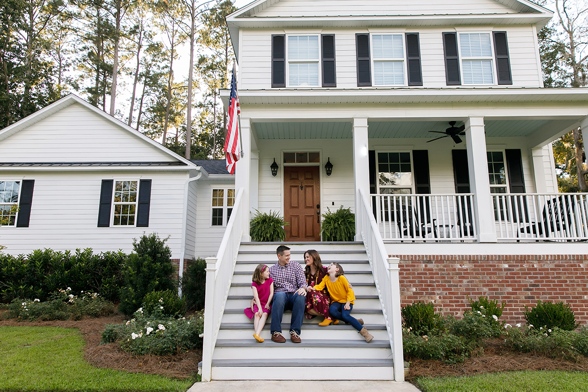 Family sitting outside on the steps of a new construction white siding farmhouse