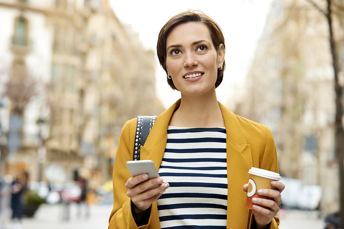 Woman with mobile phone and disposable cup in city
